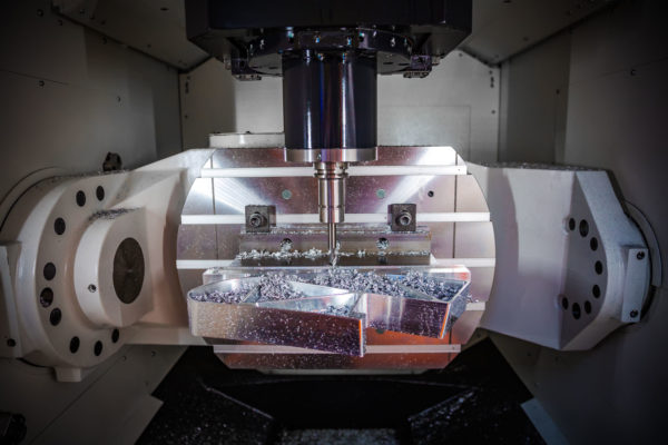 64786625 - metalworking cnc milling machine. cutting metal modern processing technology. small depth of field. warning - authentic shooting in challenging conditions. a little bit grain and maybe blurred.